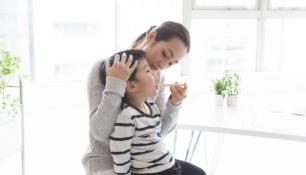 お母さんに歯を磨いてもらっている子供の写真